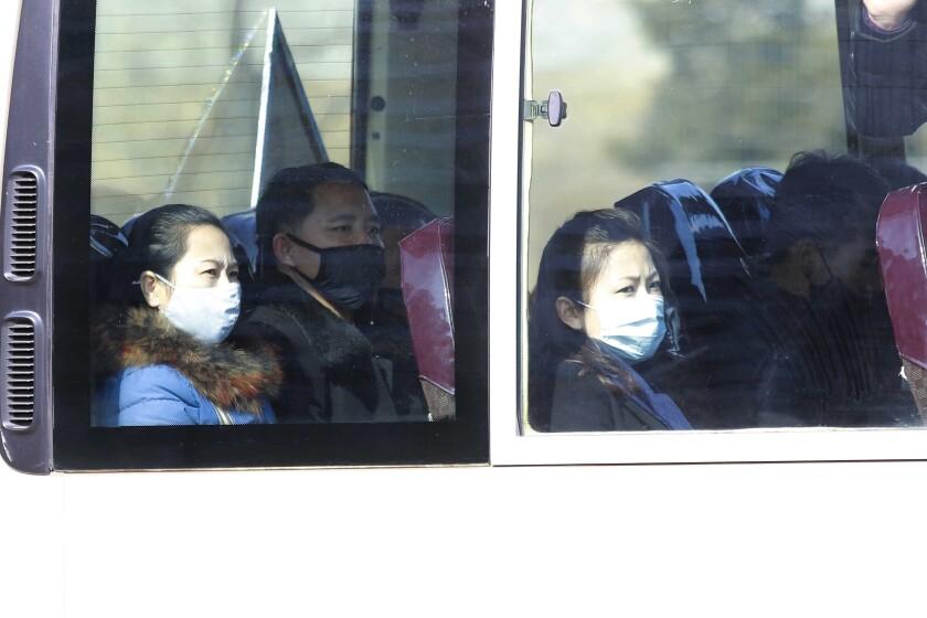 People wear masks on a bus in Pyongyang.
