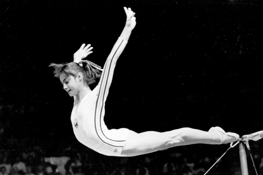 FILE - In this July 18, 1976, file photo, Romania's Nadia Comaneci dismounts from the uneven parallel bars to score a perfect 10.00 in the women's gymnastics competition at the Summer Olympic Games in Montreal. (AP Photo/Suzanne Vlamis, File)