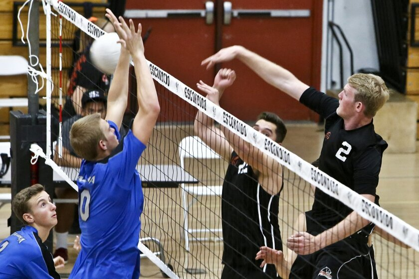 Escondido's Josh Leger (2) spikes the ball past Ramona's Calvin Harris during their second game at Escondido on Tuesday. Escondido won all three games 25-16, 25-21, 25-13.