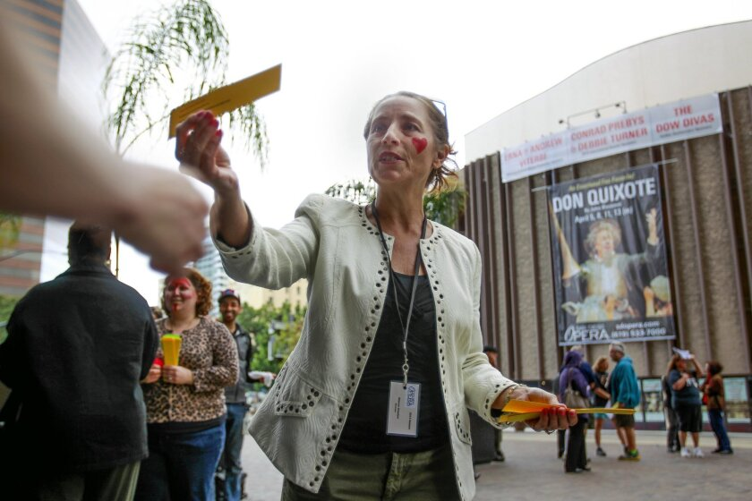With the San Diego Civic Theater behind her, Sharon Granier, one of the employees affected by the San Diego Opera's sudden closure, handed out information on signing a petition to save the San Diego Opera at the Civic Center Plaza in downtown San Diego on Thursday.