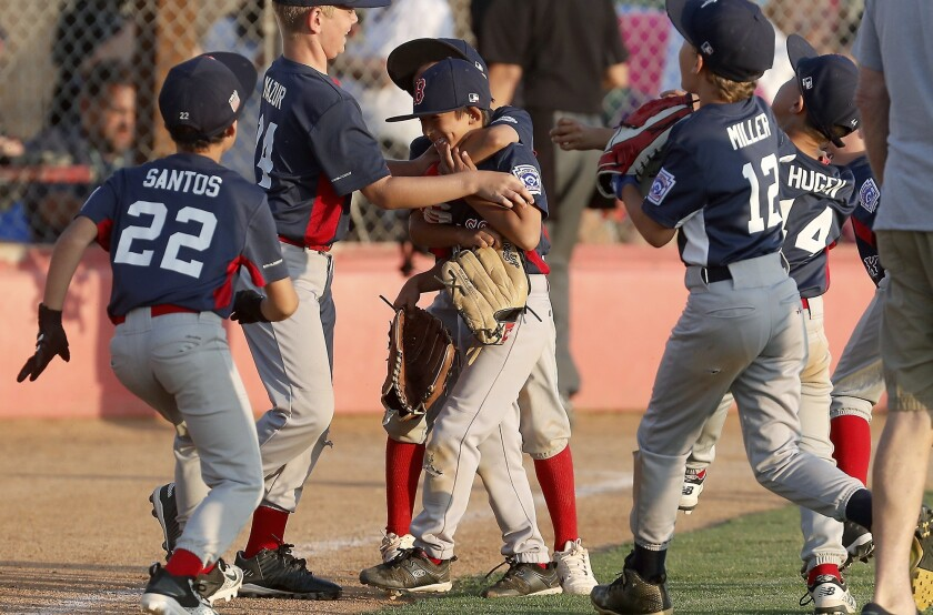 Costa Mesa American Little League closer Jordan Lee, center, is mobbed by teammates after his team d