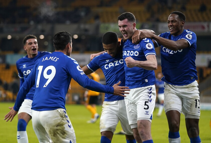 Everton's Michael Keane, second right, celebrates with teammates after scoring his side's second goal during the English Premier League soccer match between Wolverhampton Wanderers and Everton at the Molineux Stadium in Wolverhampton, England, Tuesday, Jan.12, 2021. (Tim Keeton/Pool via AP)