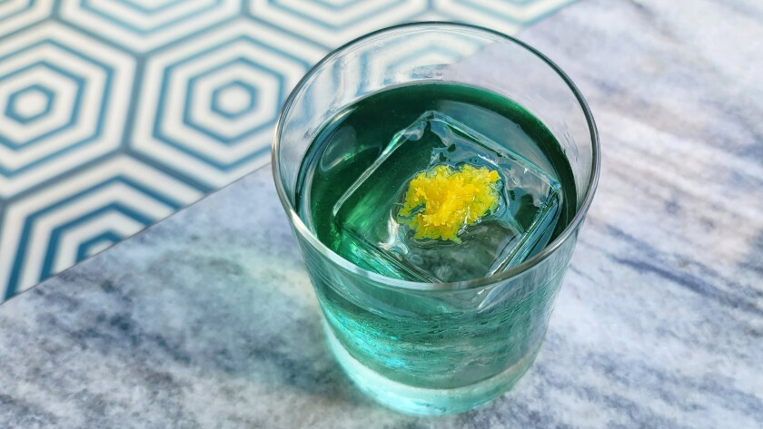A teal-colored cocktail with an ice cube that has an edible flower inside.
