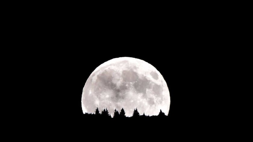 """A """"supermoon""""rises over the Dolomiti mountains in Levico Terme, north of Italy in 2014."""