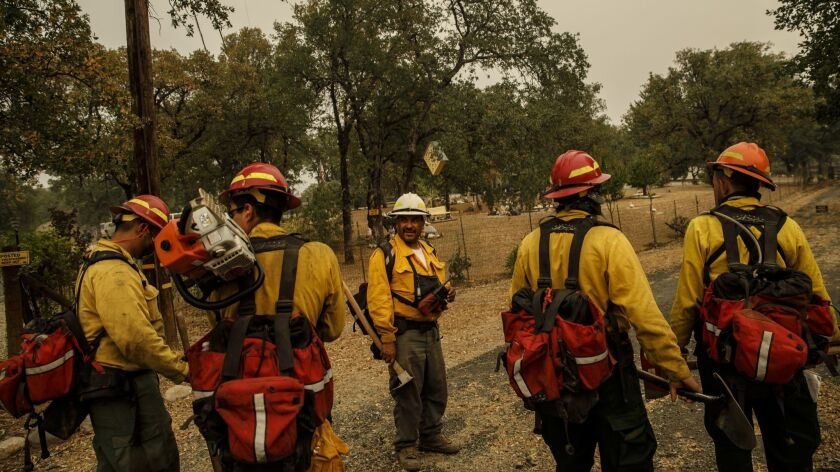 Frederico Rocha Sr., center, leads his firefighters as they mop up hot spots near homes in Redding, Calif., on July 30, 2018.
