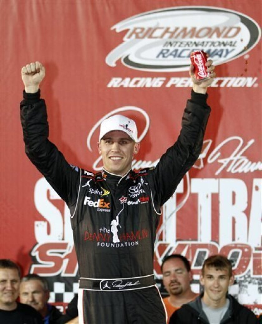 FILE - In this April 28, 2011 file photo, Denny Hamlin celebrates after winning the Denny Hamlin Foundation Short Track Showdown auto race at Richmond International Raceway in Richmond, Va. Hamlin won't compete in his annual charity race at home track Richmond because of the back injury that has si