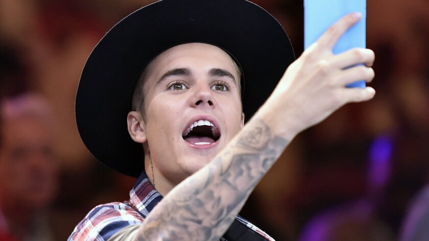 Singer Justin Bieber wields his cellphone camera at a June fight in Las Vegas.