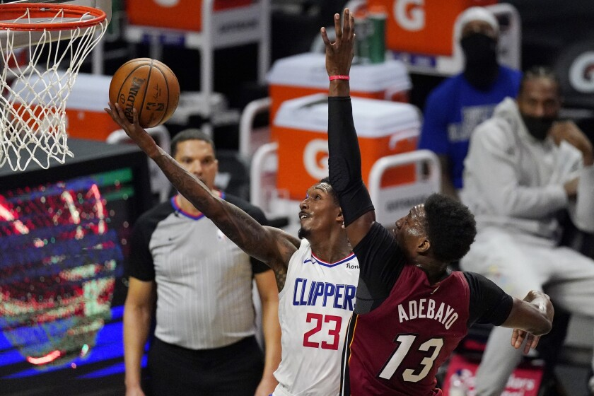 Los Angeles Clippers guard Lou Williams, left, shoots as Miami Heat center Bam Adebayo defends during the first half of an NBA basketball game Monday, Feb. 15, 2021, in Los Angeles. (AP Photo/Mark J. Terrill)