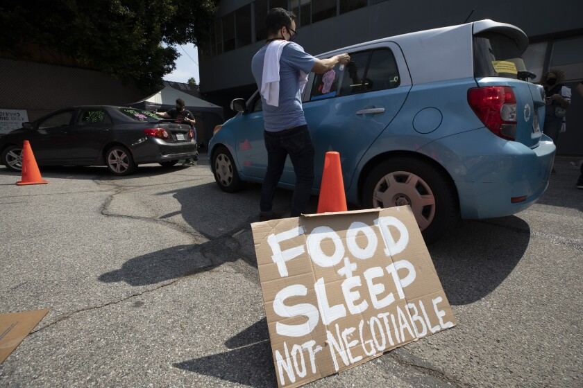"""A man paints on a car window. Beside him, a sign reads, """"Food & sleep not negotiable."""""""