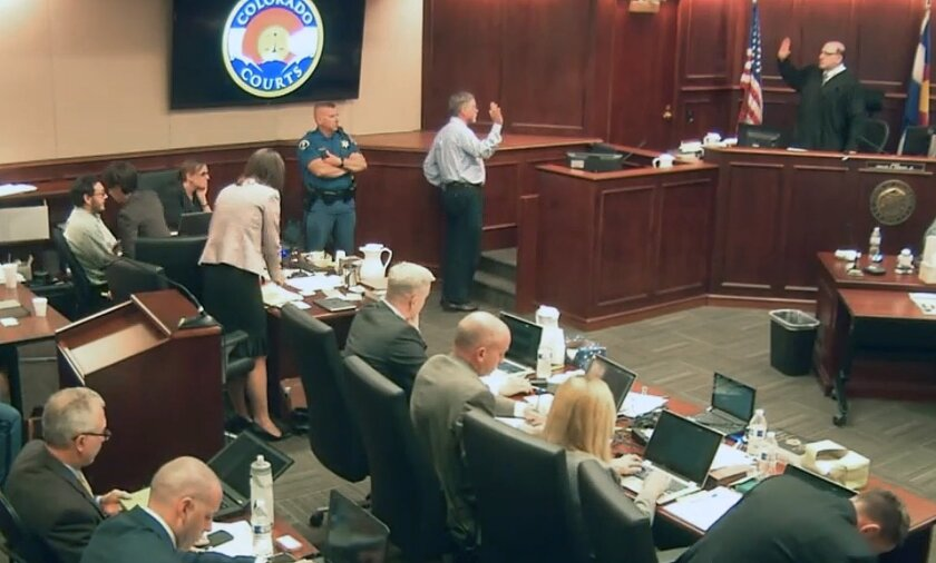 In this image taken from Colorado Judicial Department video, Robert Holmes, center top, the father of James Holmes, who is pictured at top left in light-colored shirt, is sworn in by Judge Carlos A. Samour Jr., far right, before giving testimony during the sentencing phase of the Colorado theater shooting trial, Tuesday, July 28, 2015, in Centennial, Colo. (Colorado Judicial Department via AP, Pool)