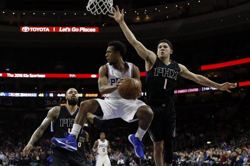 Philadelphia 76ers' Ish Smith, center, tries to pass the ball against Phoenix Suns' Devin Booker, right, and Tyson Chandler during the first half of an NBA basketball game, Tuesday, Jan. 26, 2016, in Philadelphia. (AP Photo/Matt Slocum)