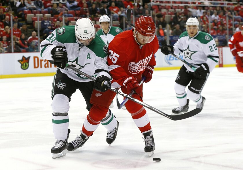 Dallas Stars center Vernon Fiddler (38) and Detroit Red Wings defenseman Mike Green (25) battle for the puck in the first period of an NHL hockey game Sunday, Nov. 8, 2015, in Detroit. (AP Photo/Paul Sancya)