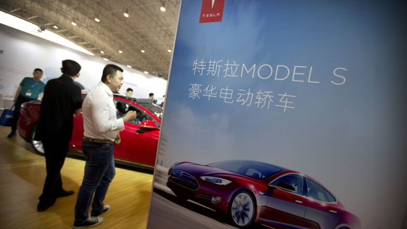 FILE - In this April 25, 2016, file photo, visitors look at a Tesla Model S electric car on display