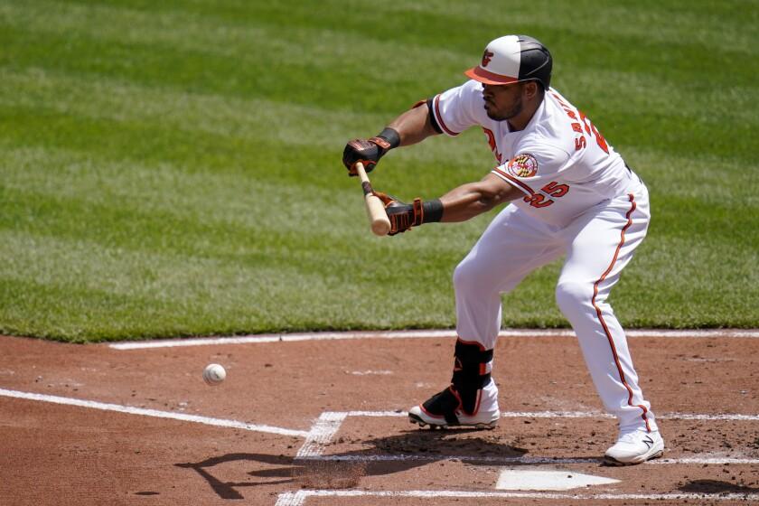 Anthony Santander de los Orioles de Baltimore ejecuta un toque de sacrificio ante los Medias Rojas de Boston, el domingo 11 de abril de 2021. (AP Foto/Julio Cortez)
