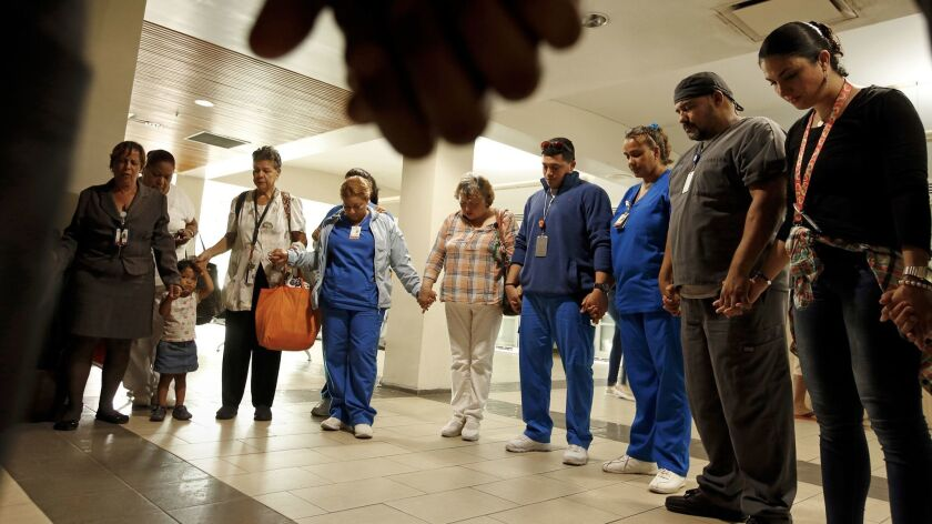 Hospital workers in San Juan pray for a colleague badly hurt in a carjacking en route to work in the