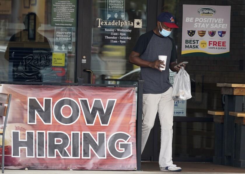 A customer walks past a now hiring sign