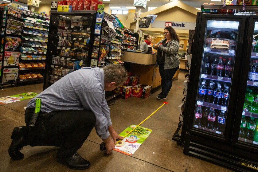 LOS ANGELES, CALIF. - MARCH 22, 2020: Workers at the Ralphs grocery store in Westchester is implementing social distancing guidelines for its customers on Sunday, March 22, 2020 in Los Angeles, Calif.. This Ralphs location is placing social distancing markers every six feet and limiting the number of customers it allows in to shop to help with social distancing due to the Coronavirus pandemic. (Jason Armond / Los Angeles Times)