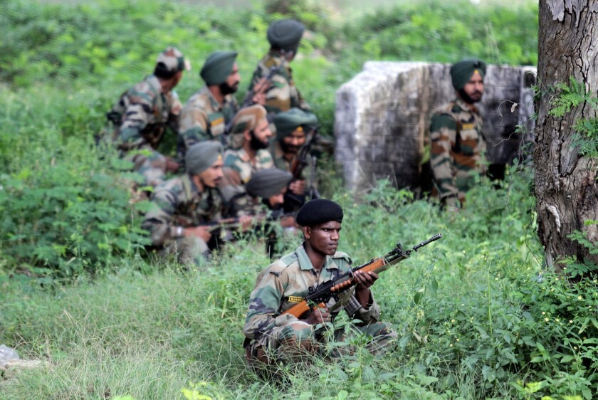 Soldiers take cover during a militant attack on a camp in India's Jammu and Kashmir state.