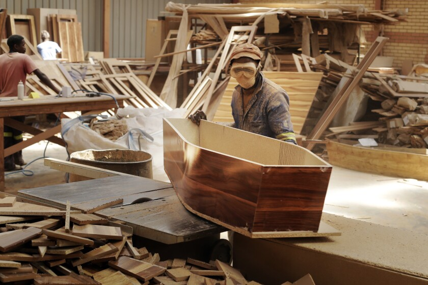 """A worker constructs coffins at Enzo Wood Designs, in Johannesburg, Wednesday, Sept. 30. 2020. Casey Pillay, a coffin-maker in South Africa, watched the coronavirus pandemic turn his business upside down. For Pillay, the need for coffins rose and fell as South Africa's lockdown levels changed, but overall, he said, """"business went down."""" As the world surpasses 1 million deaths, Africa is bracing for a likely second wave of infections. (AP Photo/Themba Hadebe)"""