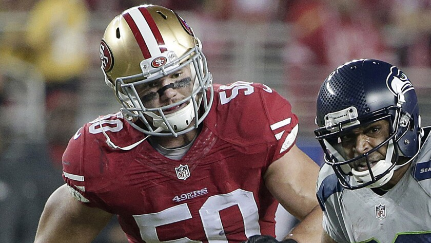 San Francisco 49ers linebacker Chris Borland, left, chases Seattle Seahawks wide receiver Doug Baldwin during a game on Nov. 27, 2014.