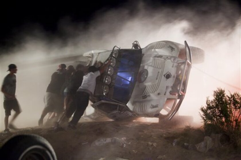 Workers push an overturned off-road race truck upright Sunday, Aug. 15, 2010 after it went out of control and ran into a crowd of spectators during a race in Lucerne Valley, Calif., on Saturday. At least eight people were killed during the incident about 100 miles east of Los Angeles.(AP Photo/Fran