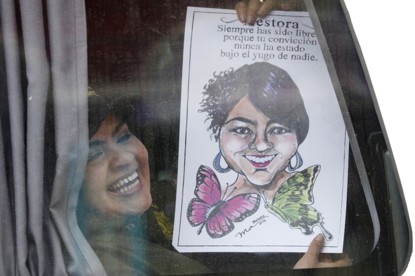 La líder comunitaria del sureño estado de Guerrero, Nestora Salgado, muestra una caricatura suya desde un autobús cuando abandona la prisión de Tepepan luego que fueran desestimados los cargos de homicidio y secuestro, en Ciudad de México, el viernes 18 de marzo de 2016. Durante una rueda de prensa posterior insistió en su inocencia y denunció en el maltrato vivido durante los más de dos años y medio que estuvo en prisión . (Foto AP / Marco Ugarte)