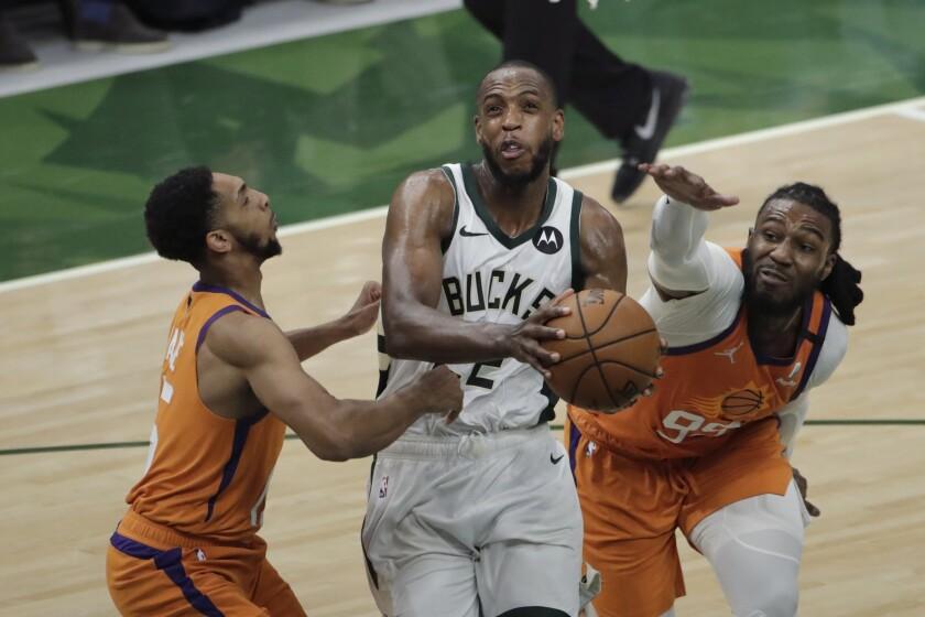 Milwaukee Bucks forward Khris Middleton drives to the basket between Phoenix Suns' Cameron Payne and Jae Crowder.