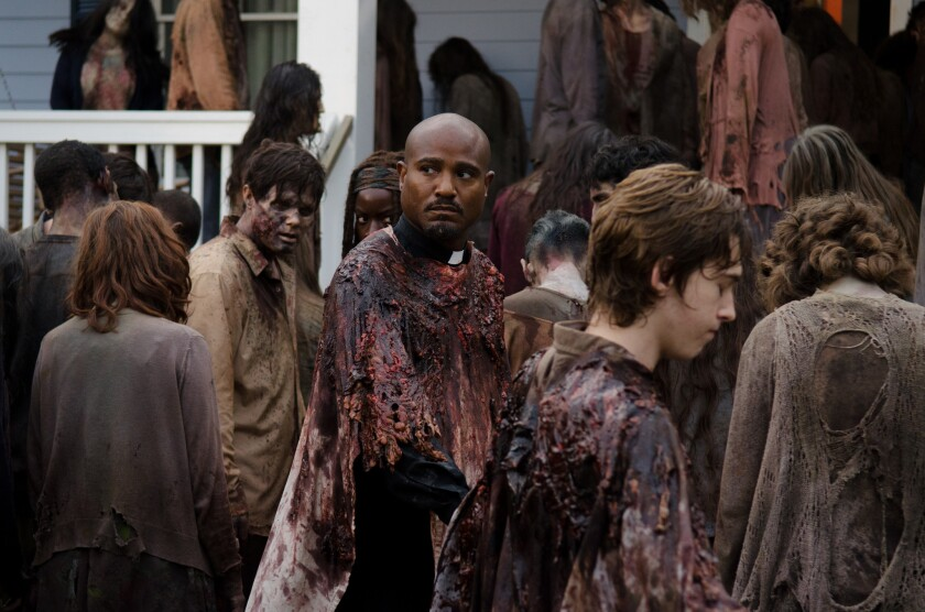 "Father Gabriel Stokes (Seth Gilliam, center) and Ron Anderson (Austin Abrams) carefully make their way through a zombie mega-herd on ""The Walking Dead."""