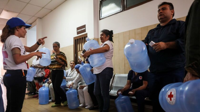 Red Cross workers deliver water purification kits to people in Caracas, Venezuela.