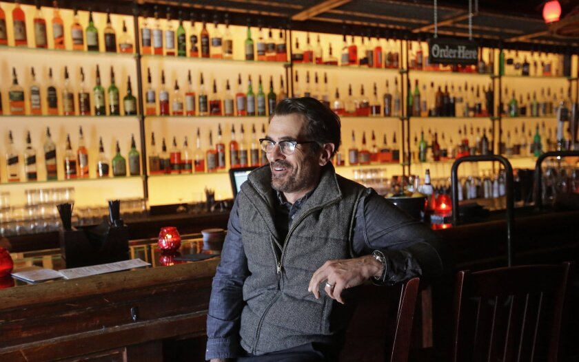 "In this April 16, 2014 photo, actor Ty Burrell, who plays bumbling dad Phil Dunphy on ABC's ""Modern Family,"" sits at the bar at Bar X, the cocktail bar he co-owns, in Salt Lake City. Burrell just opened Beer Bar, a beer garden-like eatery next door to Bar X that serves 150 beers paired up with an array of house-made bratwursts, local breads and Belgian fries. The restaurant sports long tables and benches with high ceilings to evoke that Bavarian beer hall feel. (AP Photo/Rick Bowmer)"