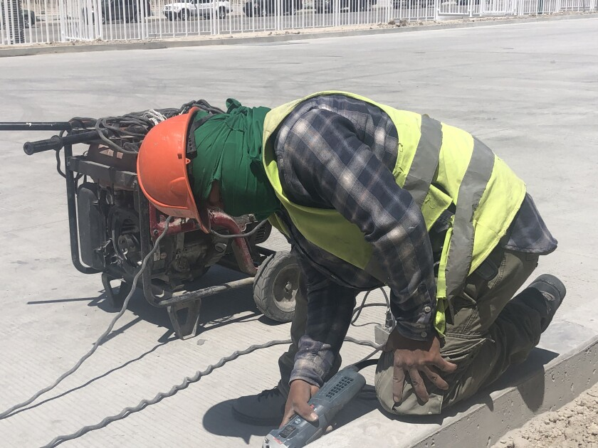 Gerson Paredes, 20, works to smooth out the edge of a curb at a factory being built on the southeastern outskirts of Tijuana. Paredes arrived in Tijuana in November 2018 with a large caravan of Central Americans.