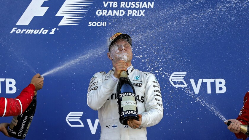 Formula One driver Valtteri Bottas is spayed with champagne by his rival on the podium after winning the Russian Grand Prix on Sunday