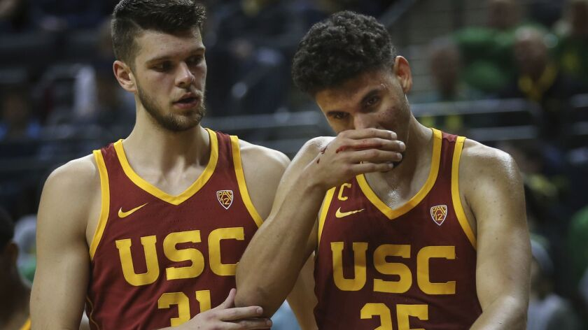 USC's Nick Rakocevic, left, helps teammate Bennie Boatwright off the floor after his nose was bloodied on a play against Oregon in the second half on Sunday.