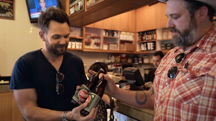 Joel McHale, left, gets bottles of Pliny the Elder handed to him from Jeremy Fraye, the general manager at The Oaks Gourmet Market. McHale, a beer fan, enjoys the hoppy flavor of Pliny and will search the city for it.