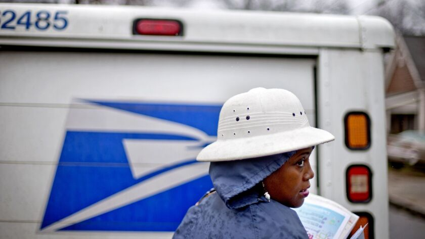 U.S. Postal Service letter carrier Jamesa Euler delivers mail in the rain in Atlanta. The Postal Service says it makes money on a deal signed with Amazon in 2013.