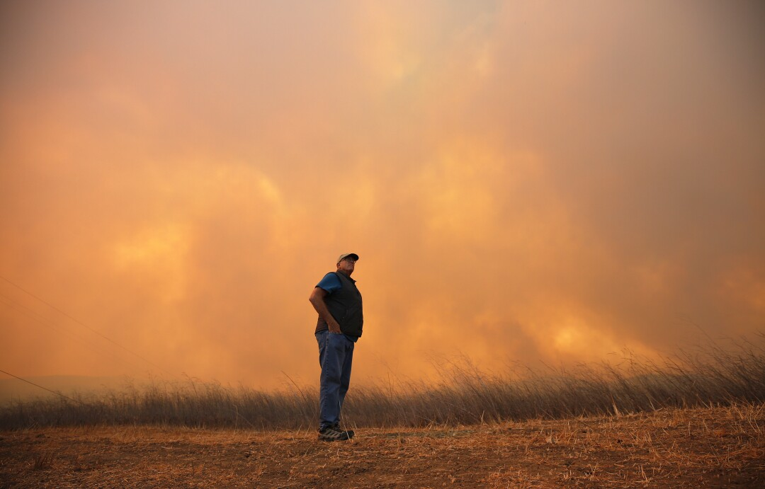A man stands near a wildfire