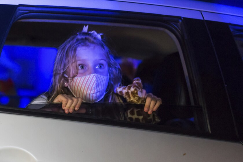 A child, wearing a protective face mask, watches a performance from inside a car, at the Hopi Hari horror theme amusement park, in the Vinhedo suburb of Sao Paulo, Brazil, Friday, Sept. 4, 2020. Due to the restrictions caused by COVID-19, the park created a drive-thru tour that allow the public to enjoy the experience by car. (AP Photo/Carla Carniel)