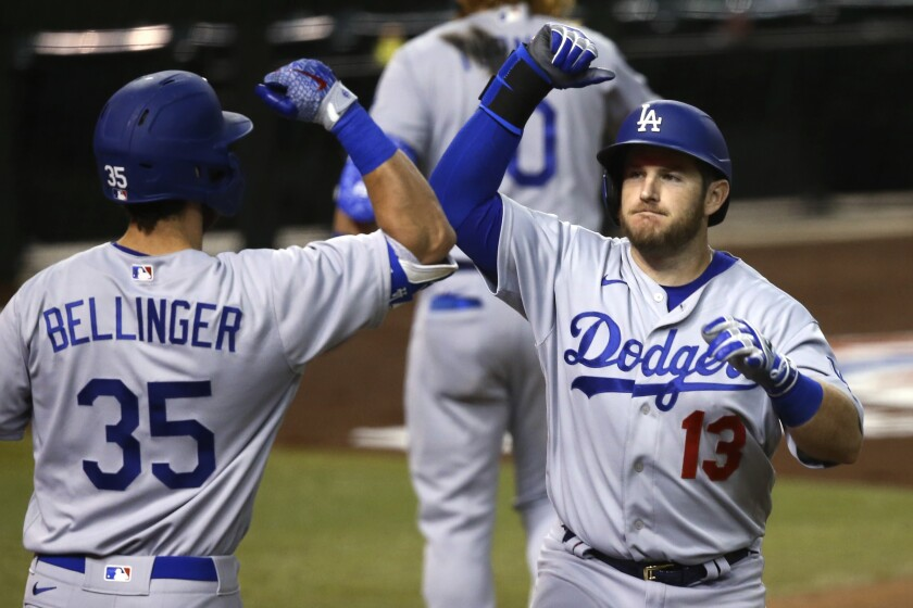 Dodgers first baseman Max Muncy, right, is congratulated by teammate Cody Bellinger.