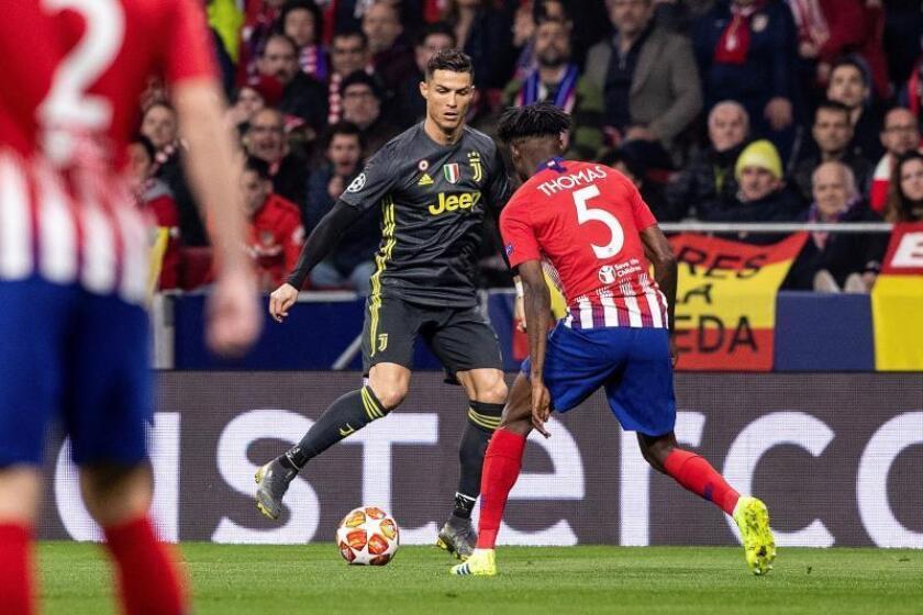 El delantero portugués del Juventus Cristiano Ronaldo (i) pelea un balón con el centrocampista ghanés del Atlético de Madrid Thomas Partey durante el partido de ida de octavos de final de la Liga de Campeones que se disputó en el Estadio Wanda Metropolitano en Madrid . EFE
