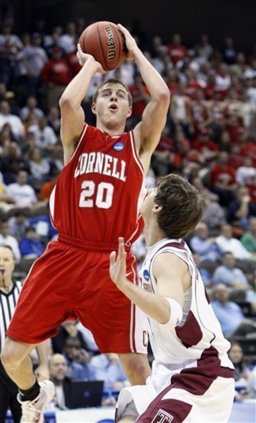 Cornell's Ryan Wittman (20) goes for a basket as Temple's  Juan Fernandez defends during an NCAA first-round college basketball game in Jacksonville, Fla., Friday, March 19, 2010.  (AP Photo/Wilfredo Lee)