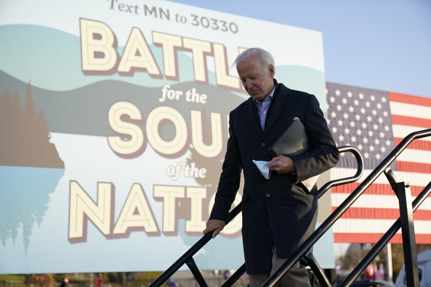 Democratic presidential candidate former Vice President Joe Biden holds his face mask after speaking at a rally at the Minnesota State Fairgrounds in St. Paul, Minn., Friday, Oct. 30, 2020. (AP Photo/Andrew Harnik)