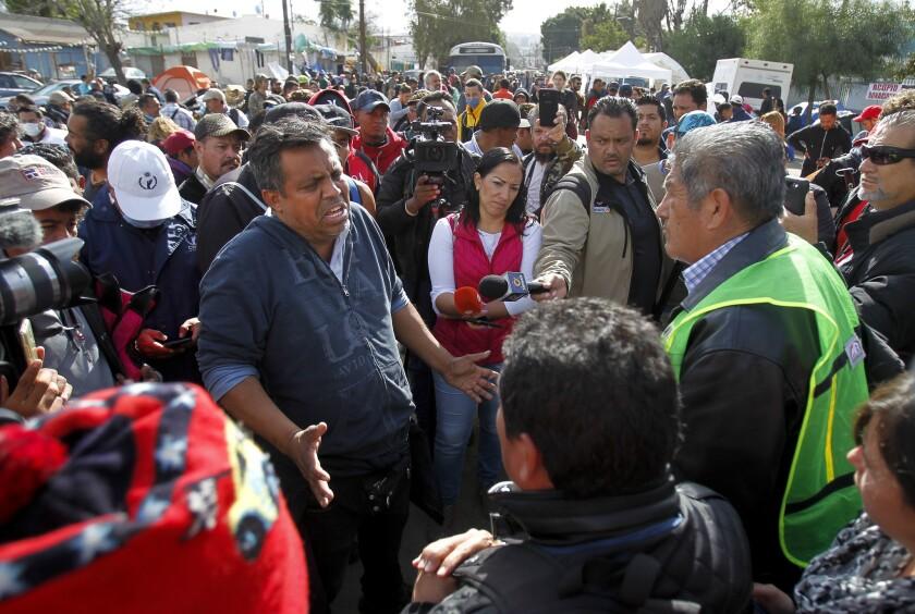 Irineo Mújica, líder de Pueblo Sin Fronteras, tiene una discusión con Sergio Tamai, a la derecha, que es el jefe de Angels Without Borders, mientras se encuentra frente al complejo deportivo Benito Juárez en Tijuana el sábado.