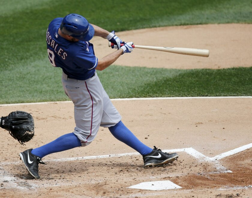 Texas Rangers' Adam Rosales hits a two-run home run off Chicago White Sox starting pitcher Chris Sale, also scoring J.P. Arencibia, during the second inning of a baseball game Wednesday, Aug. 6, 2014, in Chicago. (AP Photo/Charles Rex Arbogast)