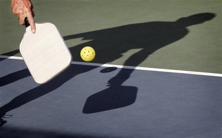 In this Monday, Dec. 3, 2012 photo, Del Teter competes in a game of pickleball at Sun City West senior community in Surprise, Ariz. A hybrid of tennis, badminton and table tennis, pickleball is played on a court a quarter the size of a tennis court, with hard rackets and a variety of whiffle ball. Created on the whim of a U.S. Congressman, pickleball has become a big hit in senior communities around the country, and is gaining steam with younger players and at schools, too. (AP Photo/Matt York)