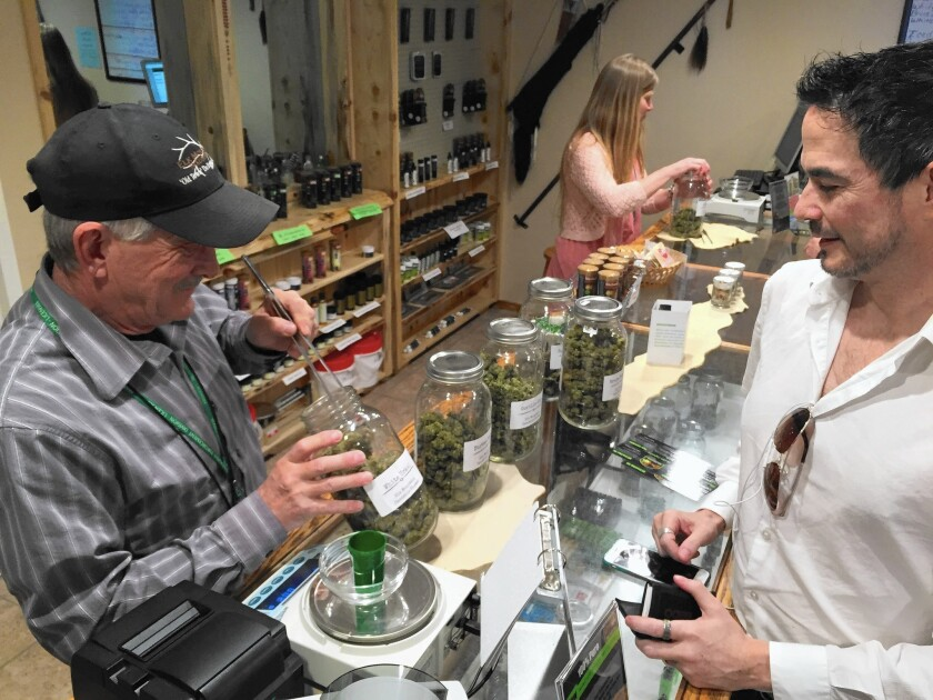 Randy Sheley helps customer Joseph Moore at Elk Mountain Trading Post, a recreational cannabis store in DeBeque, Colo. Sheley's wife, Suzanne, is also behind the counter.
