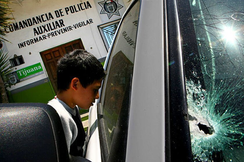 Outside a police station in the Colonia Libertad neighborhood of Tijuana, a boy peers into a police pickup damaged by gunfire. One auxiliary policeman was slain and another wounded in the attack, one of a number across the city the night before by masked gunmen that left a total of seven officers dead, and two wounded. An additional officer was injured in an earlier assault.