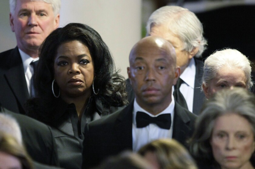 Oprah Winfrey, second from left, and Russell Simmons, center, attend the funeral of Eunice Kennedy Shriver in 2009. Winfrey will no longer produce a #MeToo documentary about Simmons premiering at Sundance this month.