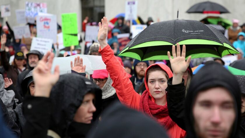 People raise their hands to signify #MeToo during the women's march Jan. 21 in Salem, Ore.