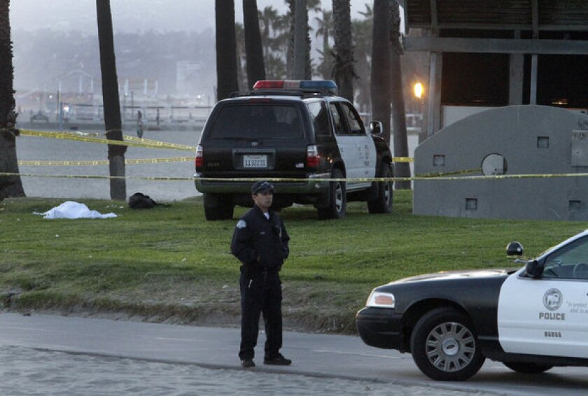An LAPD officer stands near a body found Wednesday evening by the Venice boardwalk near Breeze Avenue.
