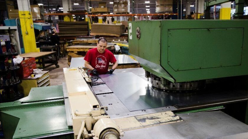 Jose Hernandez operates a turret press Oct. 18, 2018, at the Howard McCray refrigeration manufacturing facility in Philadelphia. The company had hoped to replace two 30-year-old machines that cut holes in stainless steel sheets, but that investment is on hold.